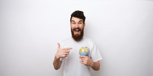 Homme barbu étonné pointant sur globe, concept de voyage