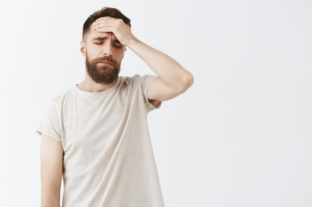 Homme barbu étourdi posant contre le mur blanc