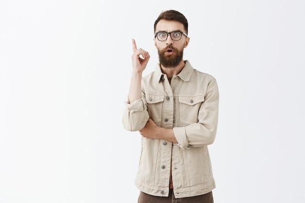 Homme barbu excité dans des verres posant contre le mur blanc
