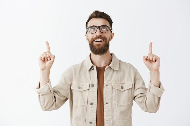 Homme barbu excité et heureux à la recherche et pointant les doigts vers le haut