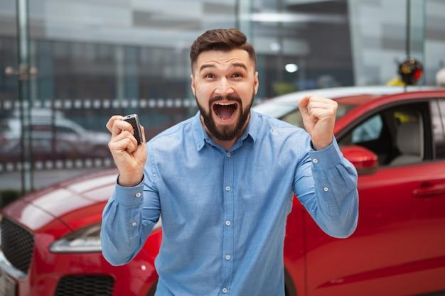 Homme barbu excité hurlant joyeusement, tenant les clés de sa nouvelle voiture.
