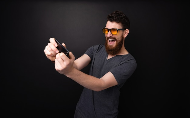 Homme barbu excité jouant sur smartphone sur fond gris foncé