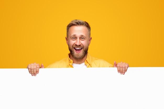 Homme barbu excité montrant une affiche vide