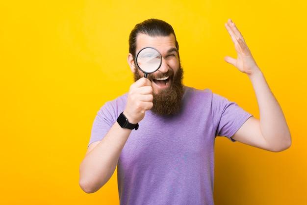 Un homme barbu excité regarde à travers une loupe la caméra.