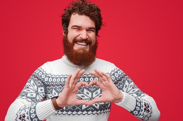 Homme barbu excité souriant et montrant le geste du cœur
