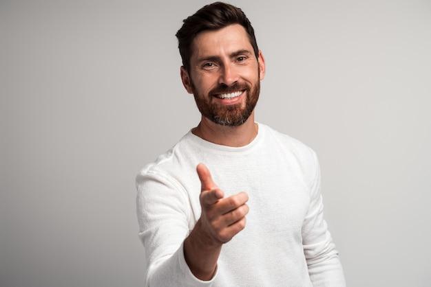 Homme barbu extrêmement heureux riant et pointant le doigt sur vous en regardant la caméra, blague ridicule et drôle. studio intérieur tourné isolé sur fond blanc