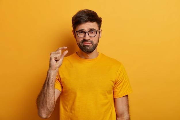 Homme barbu fait un geste de la main, conseille d'avoir une petite quantité de quelque chose