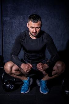 Homme barbu fitness faisant une formation de poids en soulevant de lourdes kettlebell
