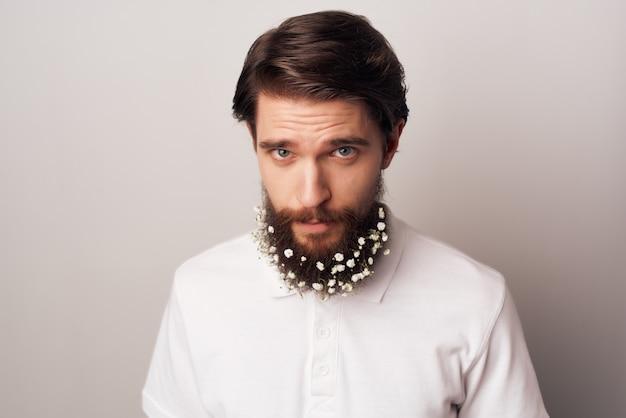 Homme barbu avec des fleurs chemise blanche émotions fond clair. photo de haute qualité