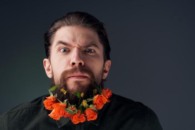 Homme barbu avec des fleurs dans une barbe dans une chemise fond isolé