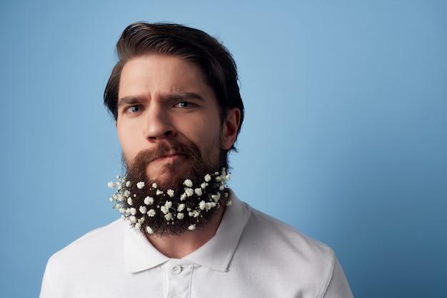 Homme barbu avec des fleurs dans le fond bleu de style de vie de soins de la peau des cheveux