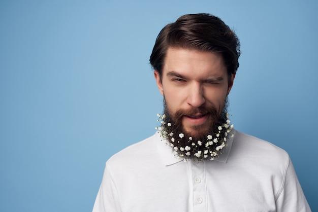 Homme barbu avec des fleurs dans sa barbe sur fond bleu