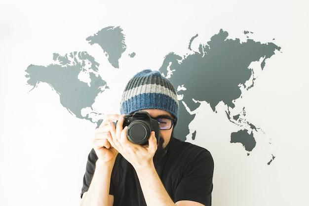 Homme barbu sur fond blanc avec carte du monde