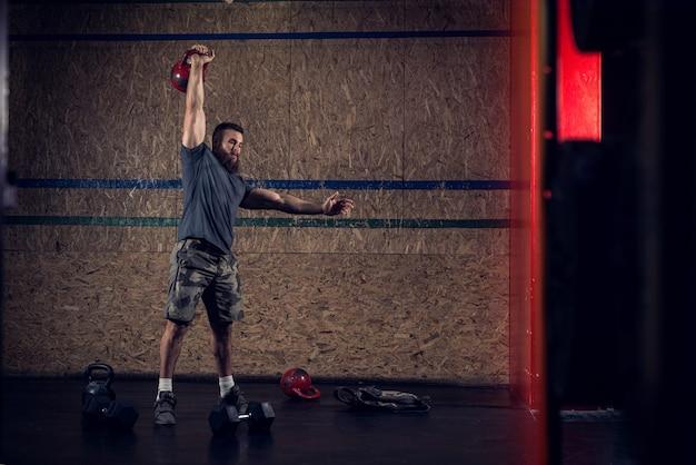 Homme barbu en forme forte soulevant des poids lourds dans une salle de formation sombre.