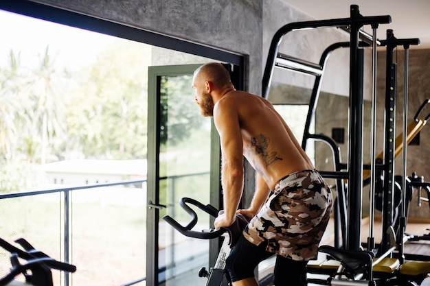 Homme barbu fort musclé tatoué travailler cardio sur vélo dans une salle de sport près de grande fenêtre avec vue sur les arbres à l'extérieur