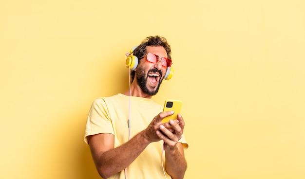 Homme barbu fou expressif écoutant de la musique avec des écouteurs et un sartphone