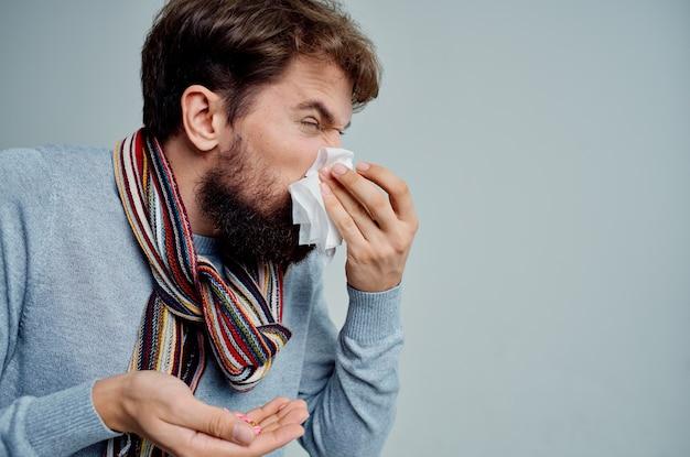 Homme barbu avec un foulard autour du cou problèmes de santé grippe fond clair