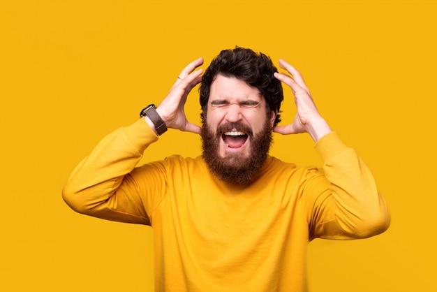 Un homme barbu frustré crie ou crie les yeux fermés et les mains près de la tête.