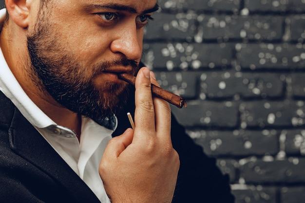 Homme barbu fumant un cigare contre le mur de briques noires
