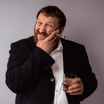 Un homme barbu fumant son cigare boit de l'alcool fort et se gratte le visage avec la main