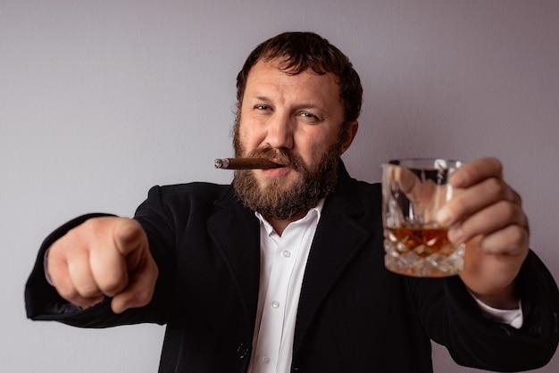 Homme barbu fumant son cigare et buvant de l'alcool fort pointant du doigt
