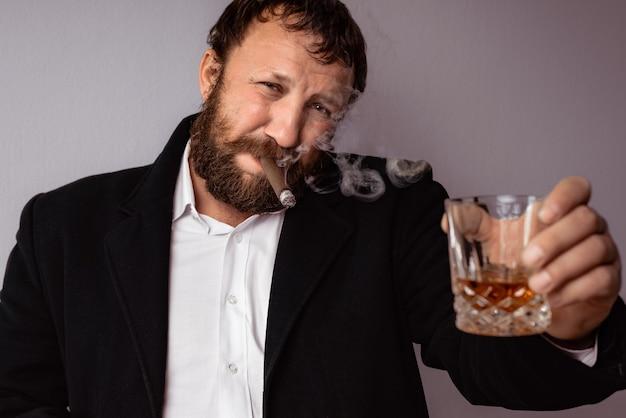Homme barbu fumant son cigare et buvant des toasts à l'alcool fort et célébrant