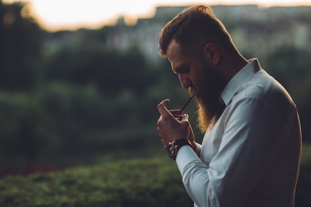 Un homme barbu fume une cigarette au coucher du soleil.