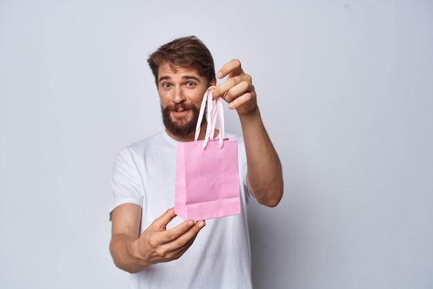 Homme barbu gai avec le fond clair de cadeau de petit paquet rose
