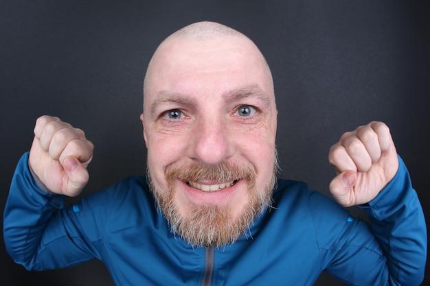Homme barbu gai avec ses mains