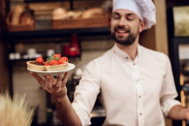 Homme barbu avec gâteau debout dans la boulangerie.