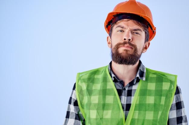 Homme barbu gilet vert casque orange workflow gestes de la main fond bleu