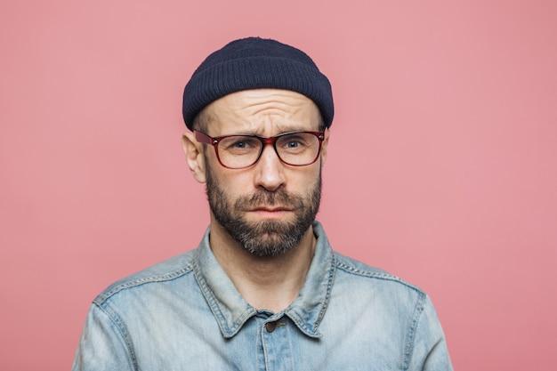 Homme barbu grincheux avec une expression offensée, insatisfait de quelque chose