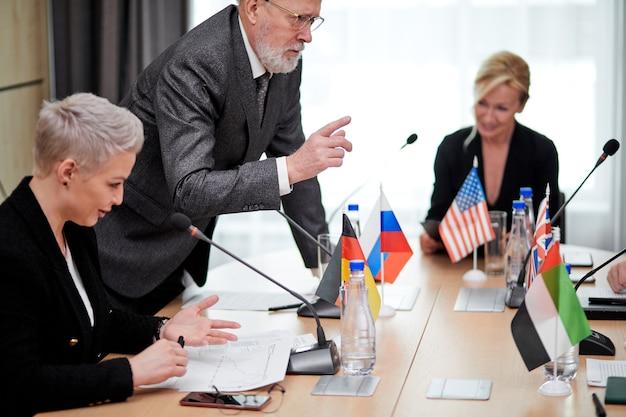 Un homme barbu gris sérieux en costume suggère constamment des idées à ses collègues assis au bureau dans le bureau