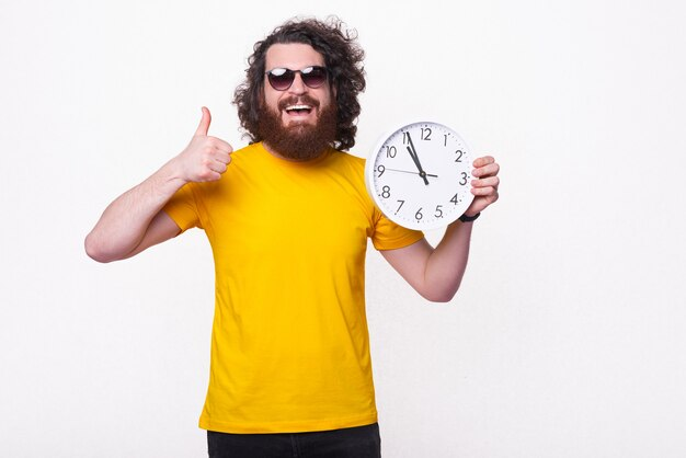 Un homme barbu heureux tient une grande horloge blanche et souriant montre un pouce vers le haut