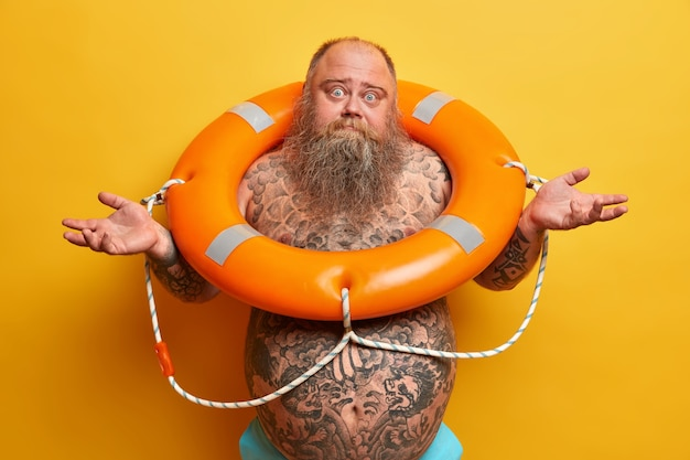 Un homme barbu incertain avec un gros ventre tatoué, écarte les mains sur le côté, se sent douteux et hésitant, se tient dans une bouée orange, apprend à nager, isolé sur un mur jaune. temps pour nager