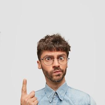 Un homme barbu indigné regarde en colère, a une expression de mécontentement, pointe vers le haut avec l'index