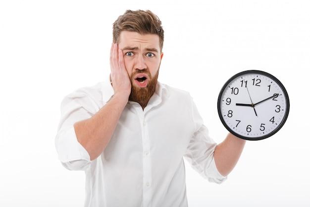 Homme barbu inquiet dans des vêtements d'affaires tenant horloge