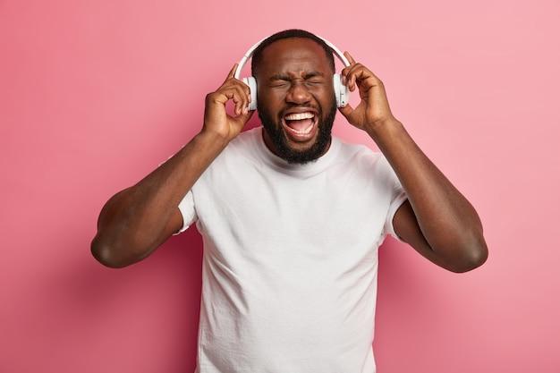 Un homme barbu insouciant détendu et émotionnel écoute la chanson préférée de la liste de lecture, divertit à l'intérieur, porte des écouteurs blancs sur les oreilles, un t-shirt décontracté, pose sur un mur rose.