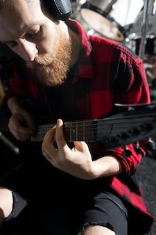 Homme barbu jouant de la guitare