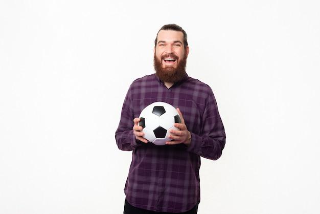 Homme barbu joyeux en chemise tenant un ballon de football et équipe de soutien