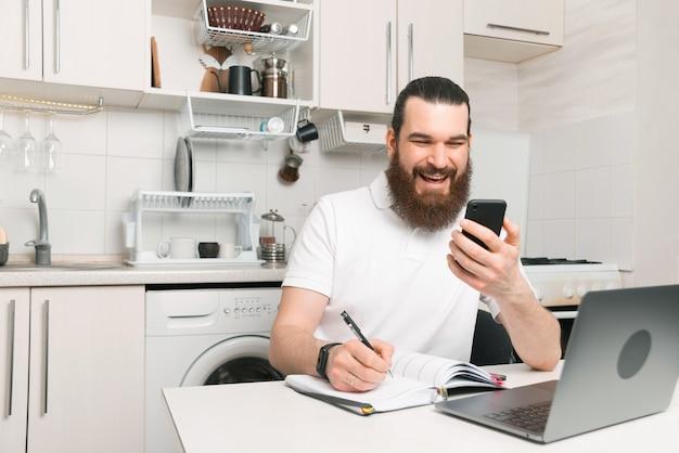 Un homme barbu joyeux est en train de parler au téléphone tout en écrivant dans son agenda.