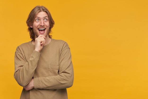 Homme barbu joyeux, positif et excité avec une coiffure blonde. porter un pull beige. touchant son menton et souriant. regarder vers la droite à l'espace de copie, isolé sur mur jaune