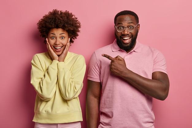 Un homme barbu joyeux souriant à lunettes montre sa petite amie qui rit joyeusement avec les mains sur les joues, exprime le bonheur et la positivité