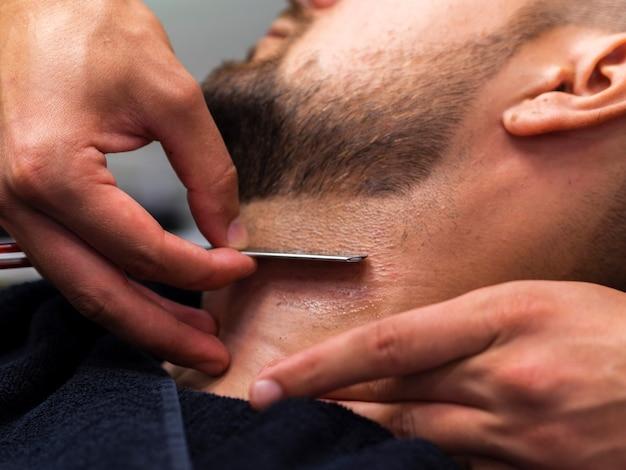 Homme barbu avec une lame de rasoir
