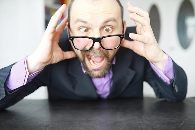 Un homme barbu louche regarde dans le cadre. maladie des yeux. le concept d'un spécialiste inexpérimenté. voisin espion.