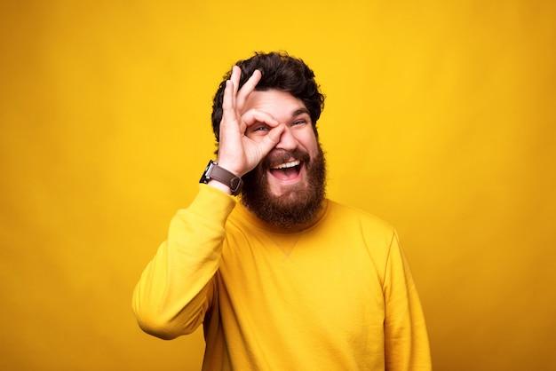 Un homme barbu ludique regarde la caméra à travers un geste correct sur son œil.