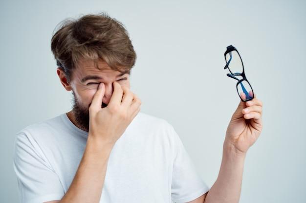 Homme barbu avec des lunettes à la main des problèmes de vision fond clair