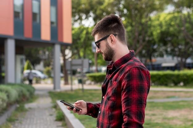 Homme barbu avec des lunettes de soleil à l'aide de smartphone