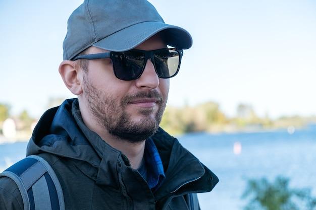Homme barbu à lunettes de soleil et une casquette de baseball avec un sac à dos