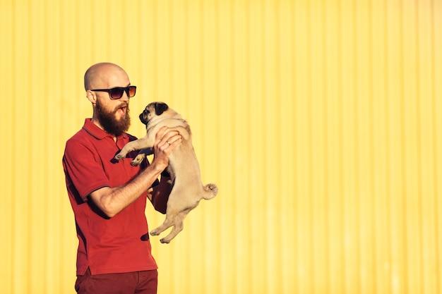 Un homme barbu à lunettes tient un chiot carlin dans ses bras contre un mur jaune